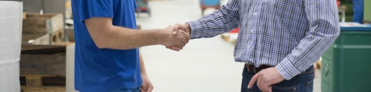 Handwerker bei der der Betriebsübergabe, schütteln sich die Hände